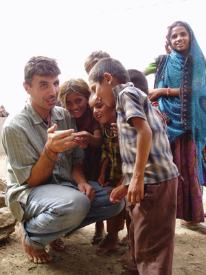 Man with children volunteering in india